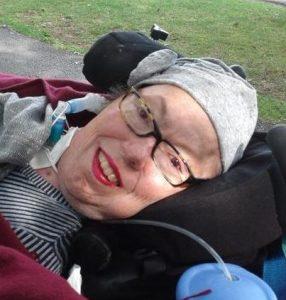 Deborah Kennard est dehors dans son fauteuil roulant récliner avec un beau sourire