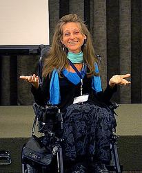 Marie-Claude Lépine est en fauteuil roulant en train de donner une conférence